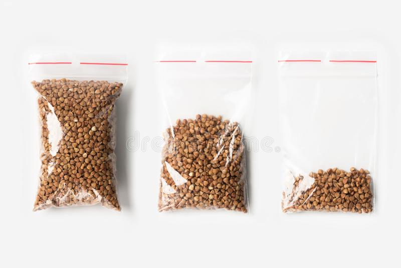 Sistema de tres VACÍOS, MEDIOS Y LLENOS bolsos transparentes plásticos de la cremallera con las avenas mondadas de alforfón super imágenes de archivo libres de regalías