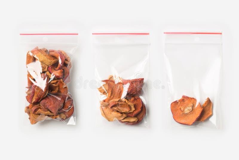 Sistema de tres VACÍOS, MEDIOS Y LLENOS bolsos transparentes plásticos de la cremallera con las manzanas secadas caseras aisladas imagen de archivo libre de regalías