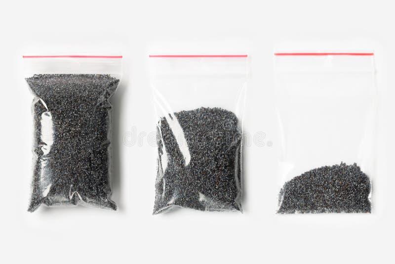 Sistema de tres VACÍOS, MEDIOS Y LLENOS bolsos transparentes plásticos de la cremallera con las semillas de amapola aisladas en b fotografía de archivo libre de regalías