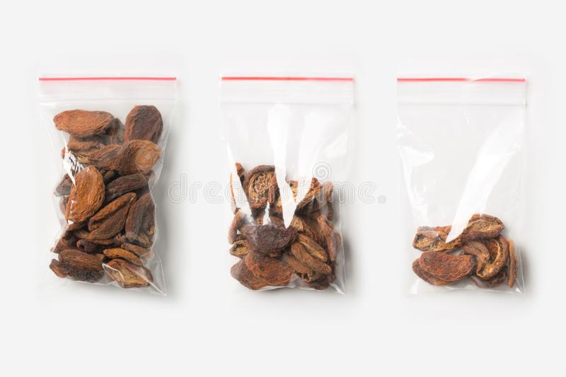 Sistema de tres VACÍOS, MEDIOS Y LLENOS bolsos transparentes plásticos de la cremallera con los albaricoques secados caseros aisl imagenes de archivo