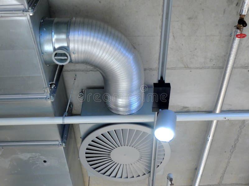 Sistema de ventilación montado en el techo concreto, el ventilador, el tubo y una lámpara imágenes de archivo libres de regalías