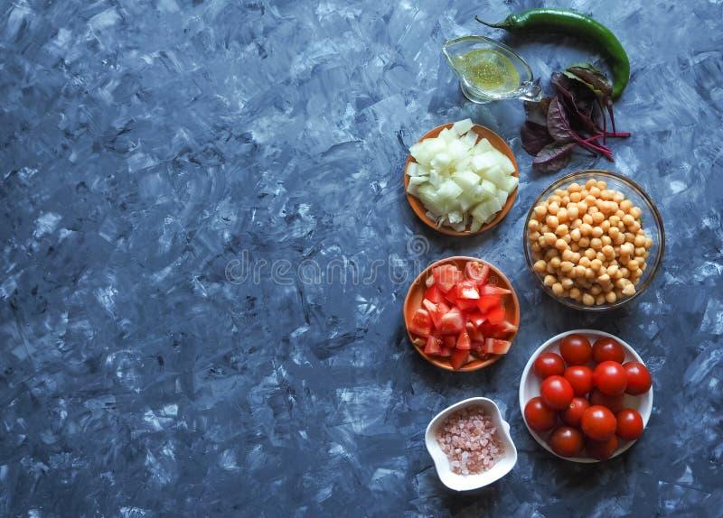Sistema de verduras con los garbanzos en fondo gris Verduras cortadas para cocinar imagen de archivo