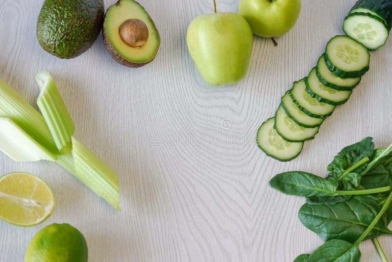 Sistema de verduras y de frutas para cocinar el cóctel verde en un fondo de madera blanco, endecha del plano fotografía de archivo