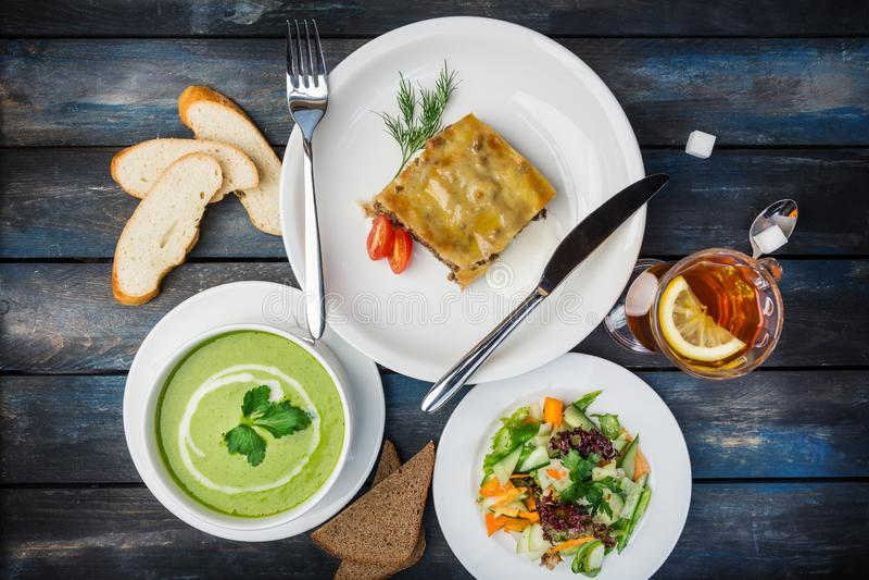 Sistema del almuerzo Lasañas, sopa y ensalada fresca de las verduras, servida con los cubiertos imágenes de archivo libres de regalías