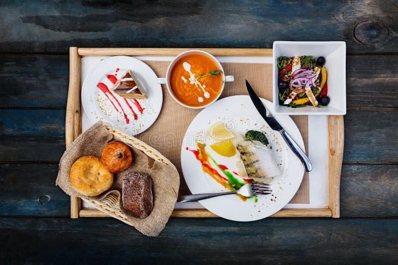 Sistema del almuerzo Pescados, sopa cocida al vapor de la calabaza y ensalada de las verduras, servidos con los cubiertos imagenes de archivo