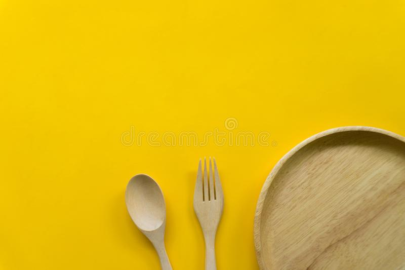 Sistema del artículos de cocina de la cuchara de madera y de la bifurcación de madera aisladas con el fondo amarillo fotos de archivo
