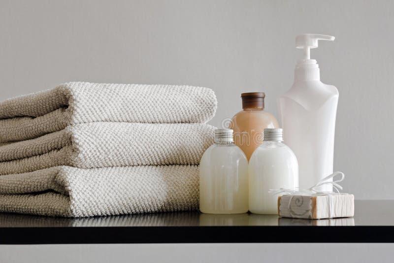 Sistema del baño y del balneario de toallas y de botellas en fondo neutral imagen de archivo libre de regalías