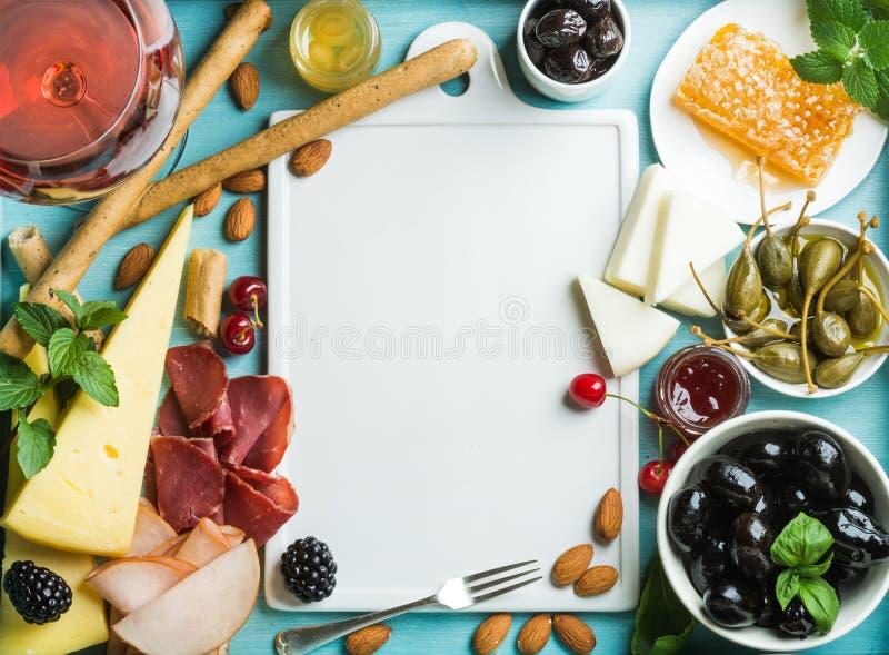 Sistema del bocado del vino del verano El vidrio de subió, carne, queso, las aceitunas, miel, las barras de pan, las nueces, las  imagen de archivo libre de regalías