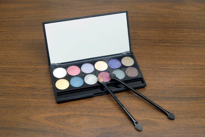 Sistema del cosmético con las sombras de ojos y los cepillos en estuche de plástico negro con el espejo en fondo de madera fotos de archivo libres de regalías