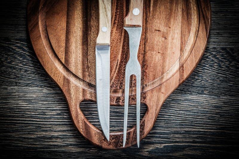 Sistema del cuchillo de la bifurcación de la carne que talla al tablero en backgroun de madera del vintage fotografía de archivo libre de regalías