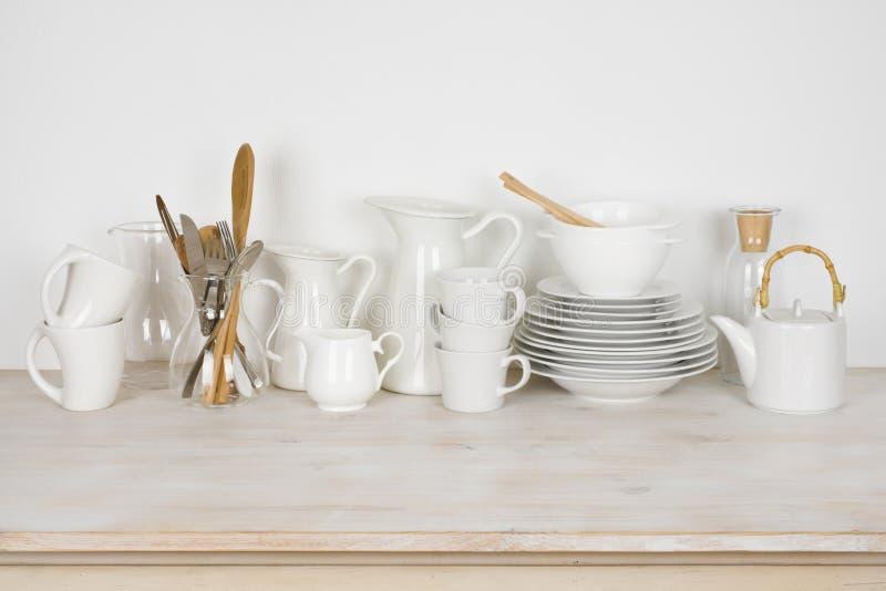 Sistema del diversos dishware y cubiertos blancos en la tabla de madera fotografía de archivo libre de regalías