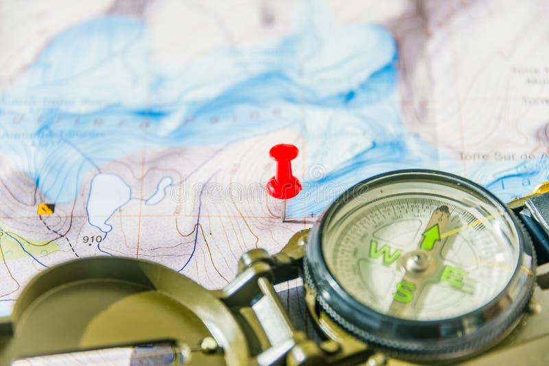 Sistema del mapa, del perno rojo del empuje y del compás para el viajero acertado foto de archivo