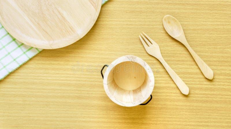 Sistema del primer de la visi?n superior del utensilio de madera de los cubiertos Bifurcación, cuchara, placa y cubo de madera en fotografía de archivo libre de regalías