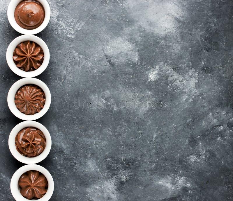 Sistema del remolino de la crema del chocolate en pequeños cuencos blancos imágenes de archivo libres de regalías