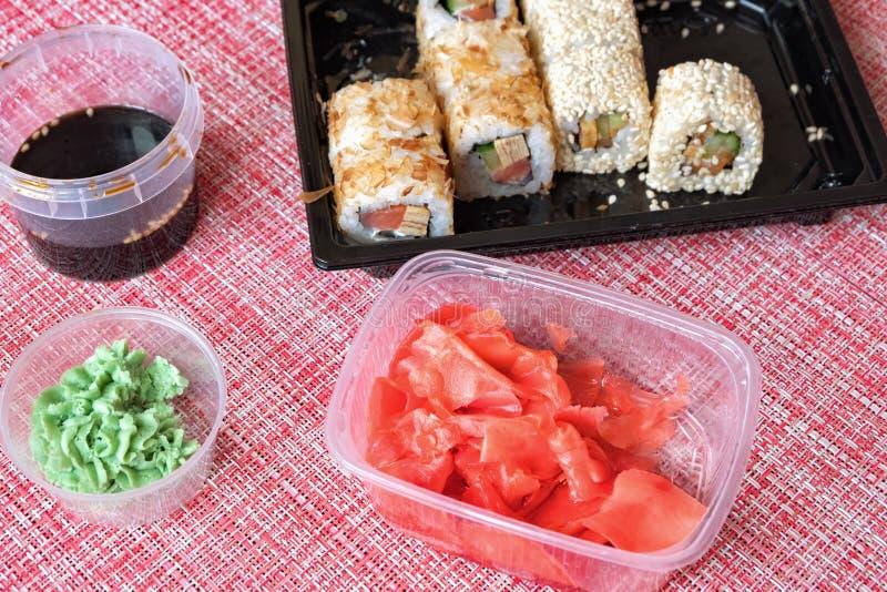 Sistema del rollo de sushi, salsa de soja, jengibre conservado en vinagre, wasabi en un envase disponible en una servilleta imagenes de archivo