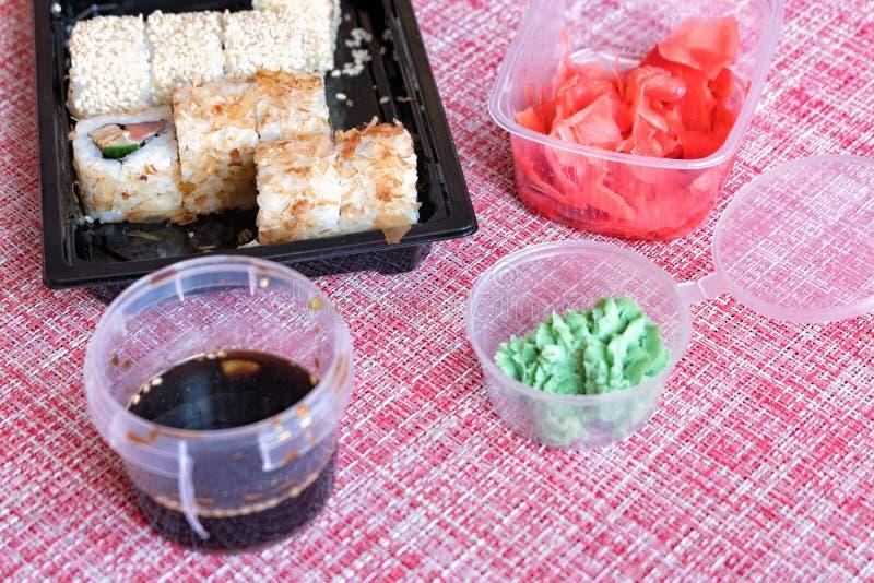 Sistema del rollo de sushi, salsa de soja, jengibre conservado en vinagre, wasabi en un envase disponible en una servilleta fotografía de archivo libre de regalías