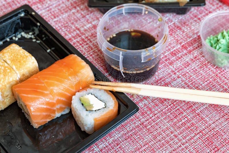Sistema del rollo de sushi, salsa de soja, wasabi, jengibre conservado en vinagre, palillos en un envase disponible en una servil fotos de archivo libres de regalías