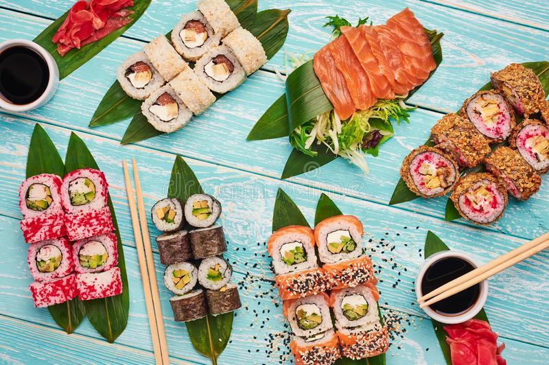Sistema del rollo de sushi sushi, sashimi, endecha plana del maki en el contexto de madera azul Cocina de Jap?n fotografía de archivo libre de regalías