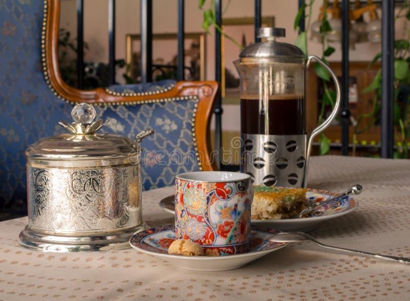 Sistema del vintage de la taza de caf?, de pote del caf?, de Baklava de la torta de miel y de cuenco de az?car Foco selectivo fotos de archivo