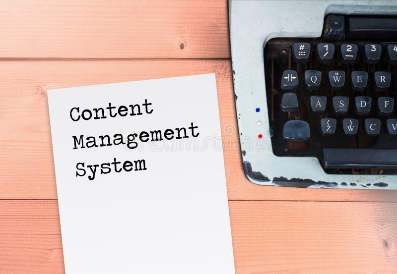 Sistema di content management su carta con la macchina da scrivere sulla tavola di legno immagini stock