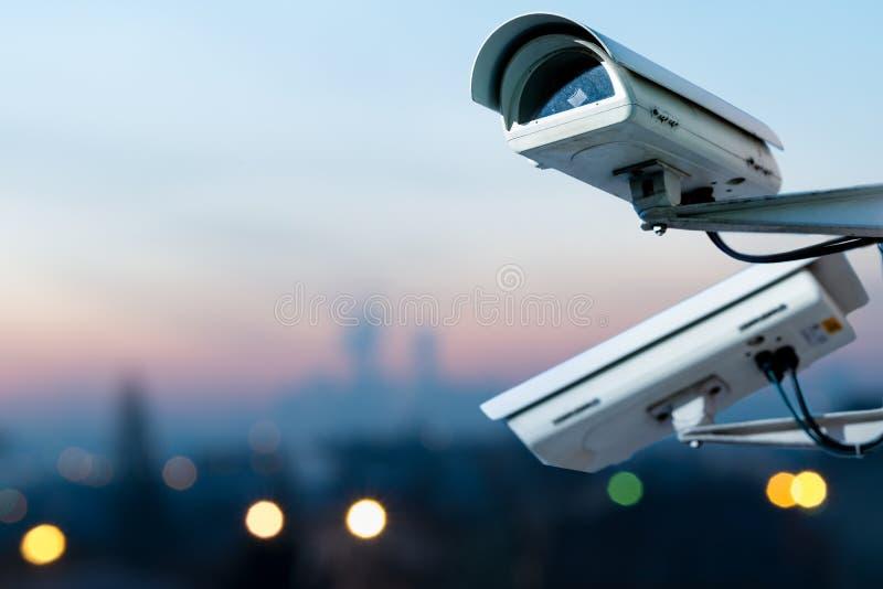 sistema di controllo della macchina fotografica del CCTV di sicurezza con la vista panoramica di una città su fondo confuso fotografie stock libere da diritti