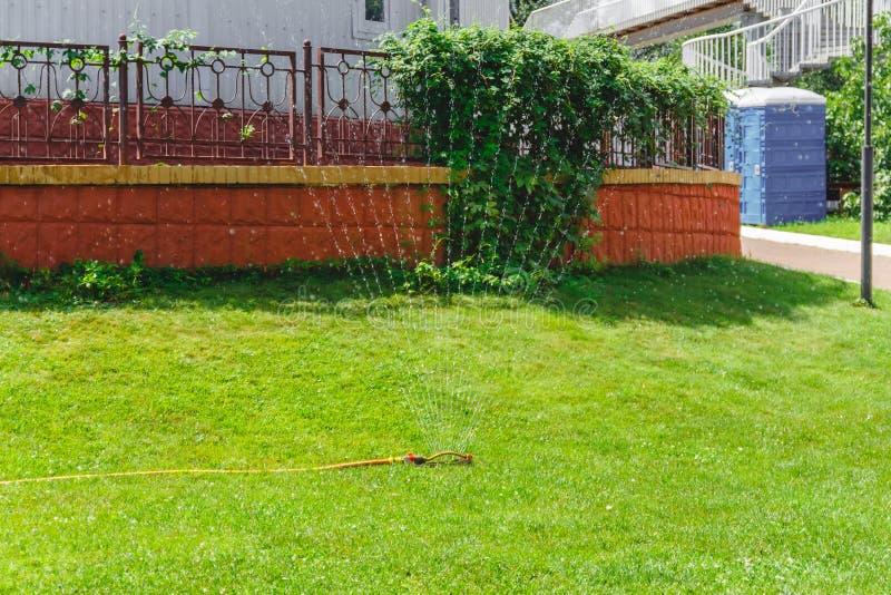 Sistema di innaffiatura della fontana del gocciolamento nel giardino vicino alla casa fotografia stock
