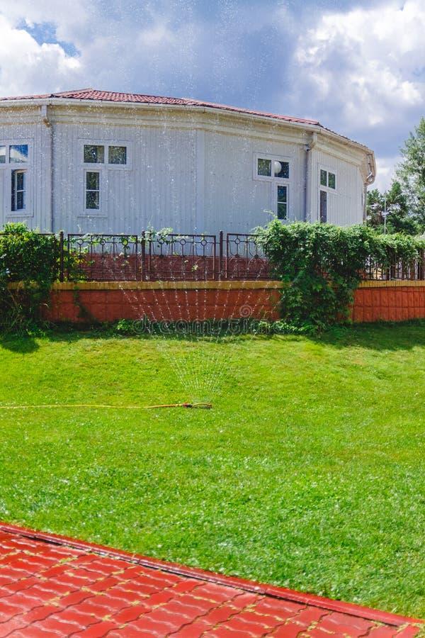Sistema di innaffiatura della fontana del gocciolamento nel giardino vicino alla casa fotografie stock libere da diritti