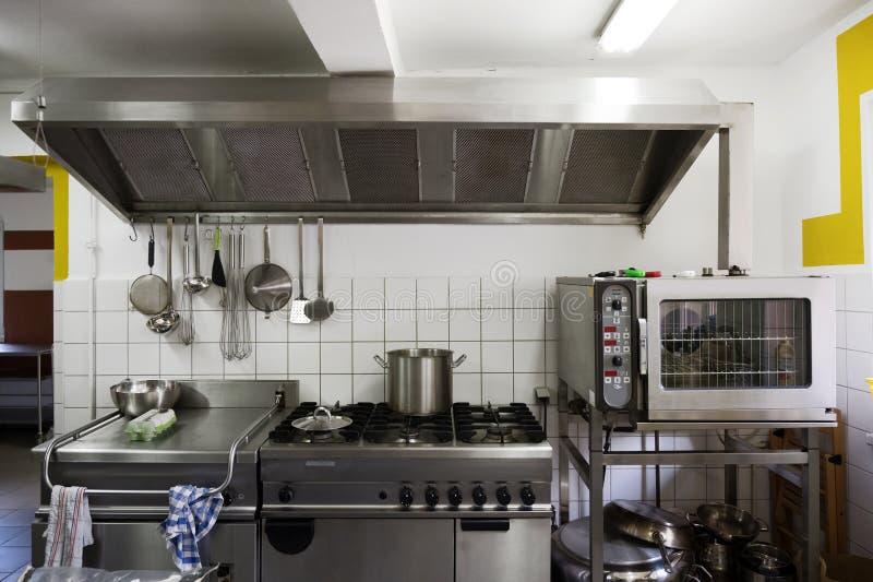 Sistema do fogão do aço com a capa do fogão, da grade, do forno e do extrator em uma cozinha profissional da cantina imagem de stock