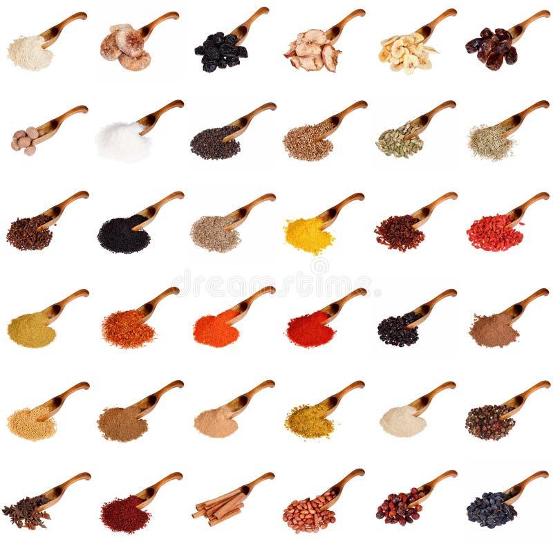 Sistema enorme de especias, de frutas secadas, de nueces, de hierbas y de habas en la cuchara de madera aislada en blanco imagenes de archivo