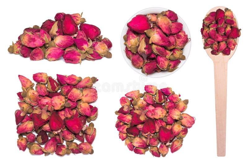 Sistema grande de té de los brotes color de rosa secos aislados en blanco Rosas secas en cuchara de madera fotos de archivo