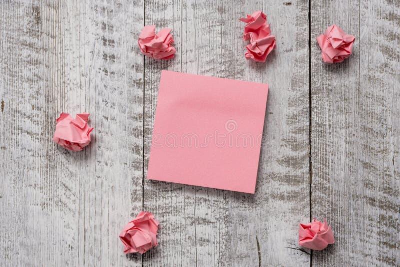 Sistema grueso de papel de nota llano con los pedazos en la tabla texturizada de madera Las hojas en blanco rosadas y trashes sob imagenes de archivo