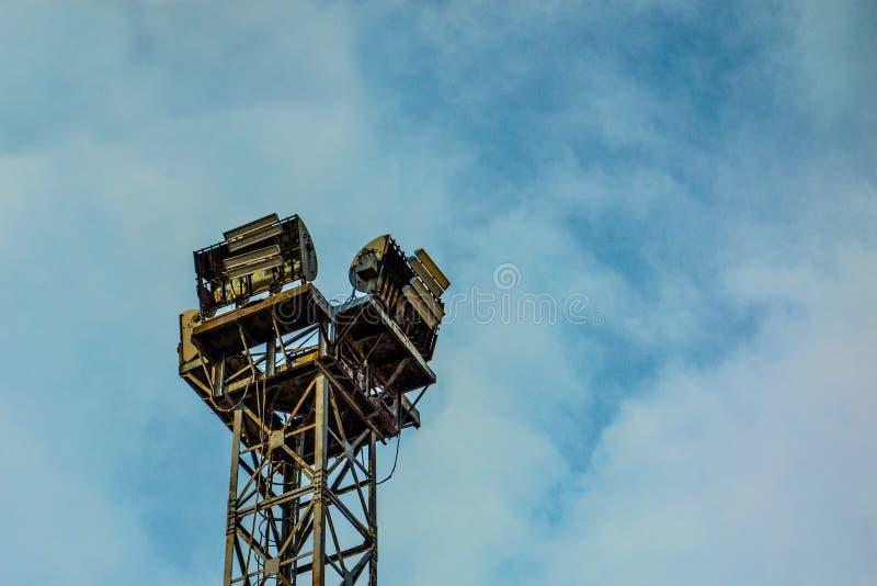 Sistema industrial enorme velho da lâmpada da luz do ponto no fundo do céu azul Construção envelhecida do quadro da torre do meta imagens de stock royalty free