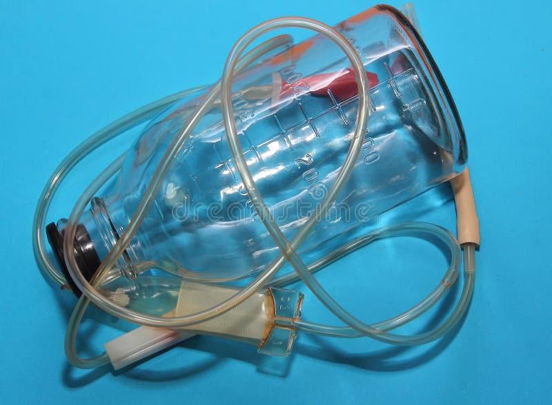 Sistema intravenoso del dropper para las drogas en fondo azul imagen de archivo