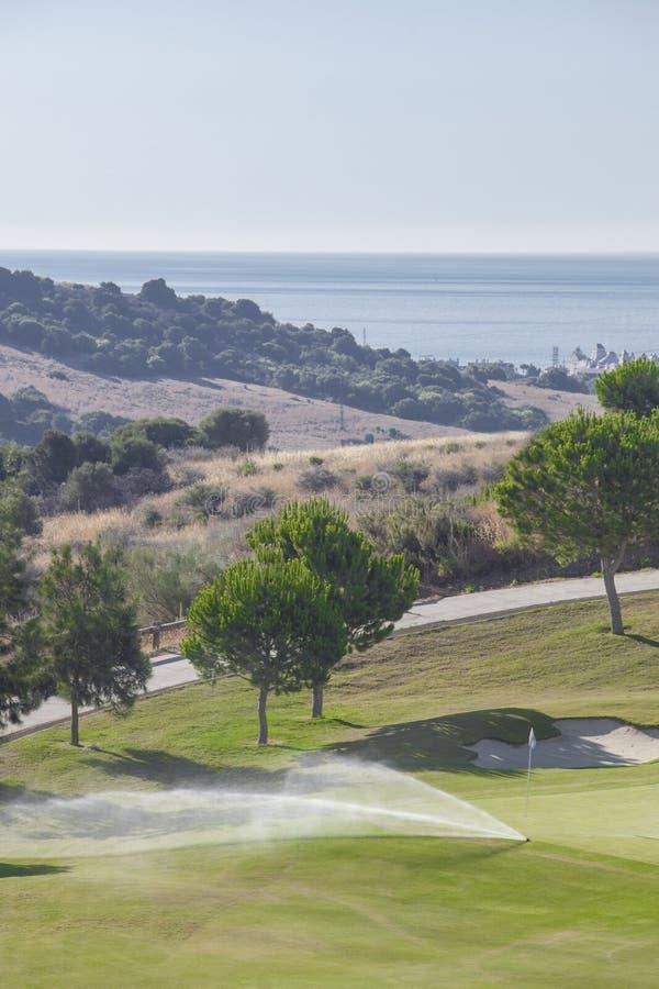 Sistema molhando que trabalha no campo de golfe verde Costa del Sol, Spain imagem de stock royalty free
