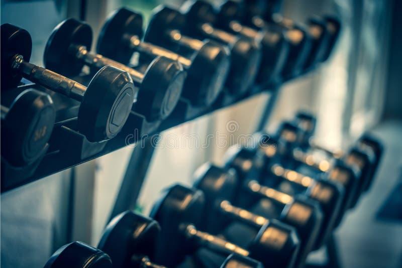 Sistema negro de la pesa de gimnasia Cierre para arriba muchas pesas de gimnasia del metal en el estante en el centro de aptitud  imágenes de archivo libres de regalías