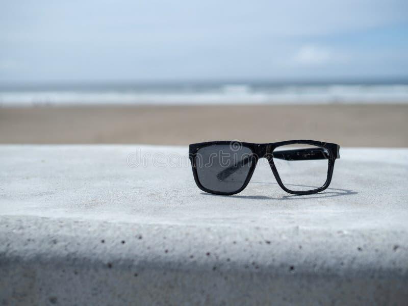 Sistema quebrado de gafas de sol que se sientan en un muro de cemento que pasa por alto imagen de archivo libre de regalías