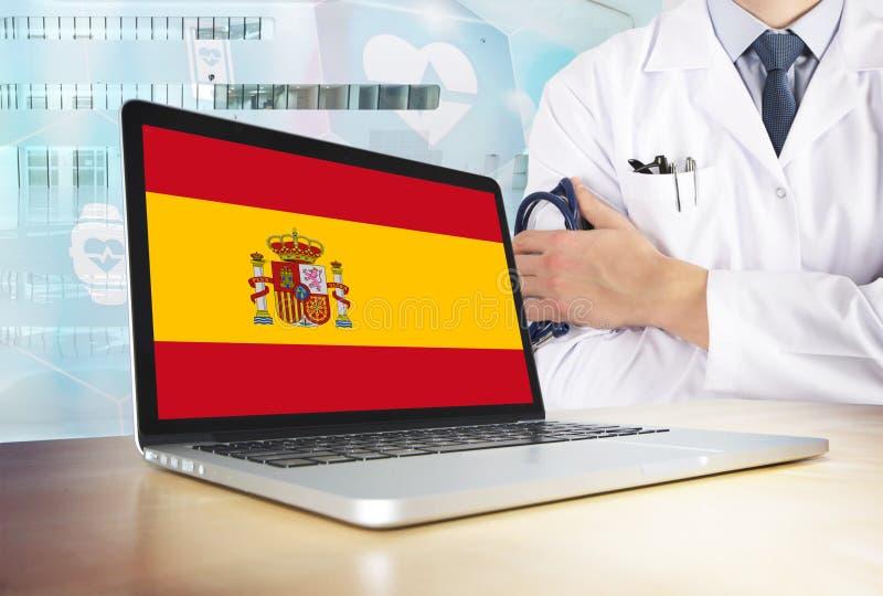 Sistema sanitario de España en tema de la tecnología Bandera española en la pantalla de ordenador Doctor que se coloca con el est foto de archivo libre de regalías
