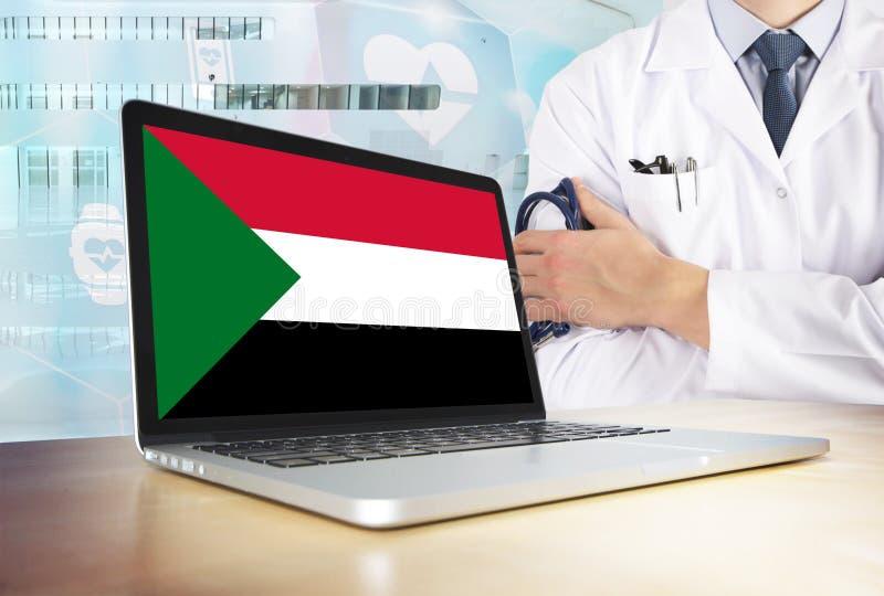 Sistema sanitario del Sudan nel tema di tecnologia Bandiera sudanese sullo schermo di computer Medico che sta con lo stetoscopio  immagine stock libera da diritti