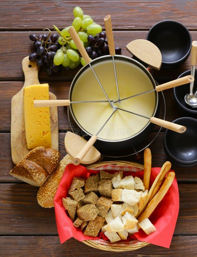 Sistema tradicional de los utensilios para la 'fondue', con pan, queso imagenes de archivo