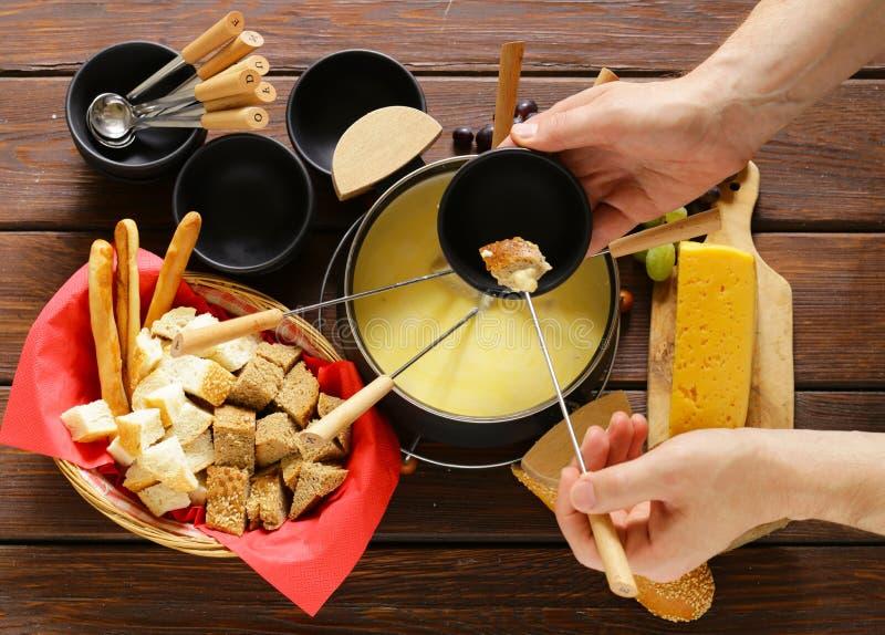 Sistema tradicional de los utensilios para la 'fondue', con pan, queso imagen de archivo libre de regalías
