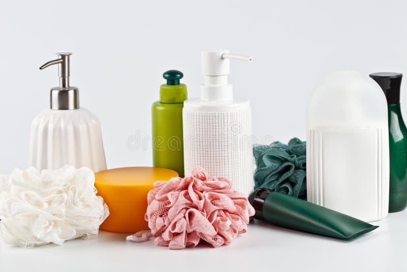 Sistema y esponjas cosméticos de productos del baño en fondo ligero foto de archivo libre de regalías