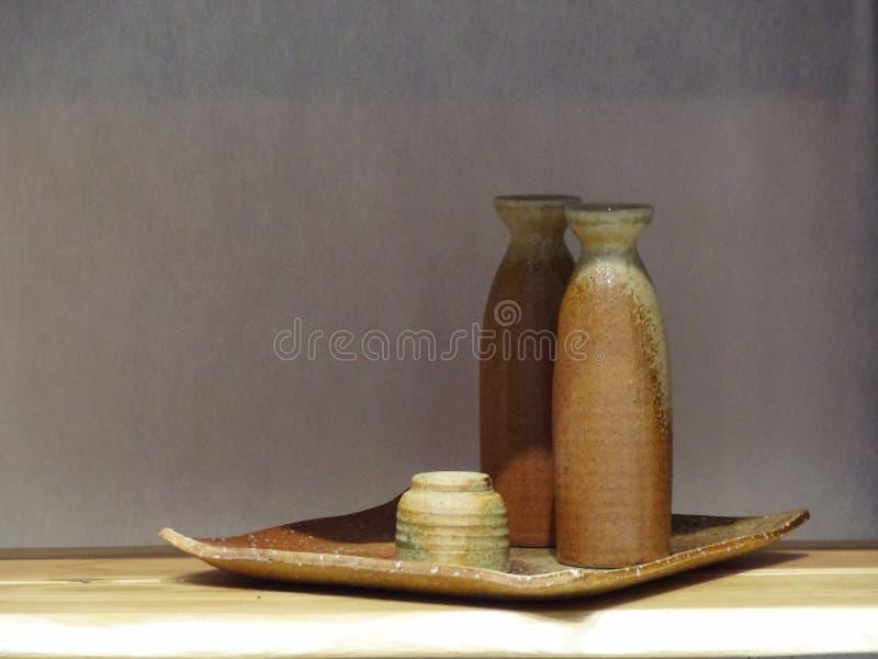 Sistemas de cerámica japoneses del motivo verde y marrón en la bandeja cuadrada con la sombra fotografía de archivo libre de regalías