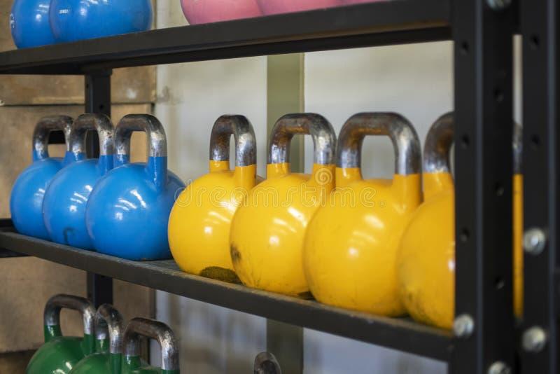 Sistemas pesados de kettlebell en los estantes del hierro en el gimnasio usado para la aptitud funcional y el entrenamiento físic imágenes de archivo libres de regalías