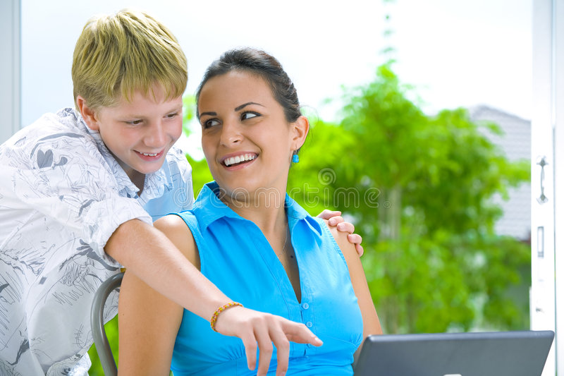 With sister. Portrait of happy family getting busy with laptop stock photography