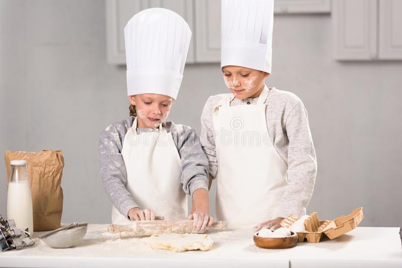 Sister and brother in aprons and chef hats making dough with rolling pin at table. In kitchen royalty free stock photography