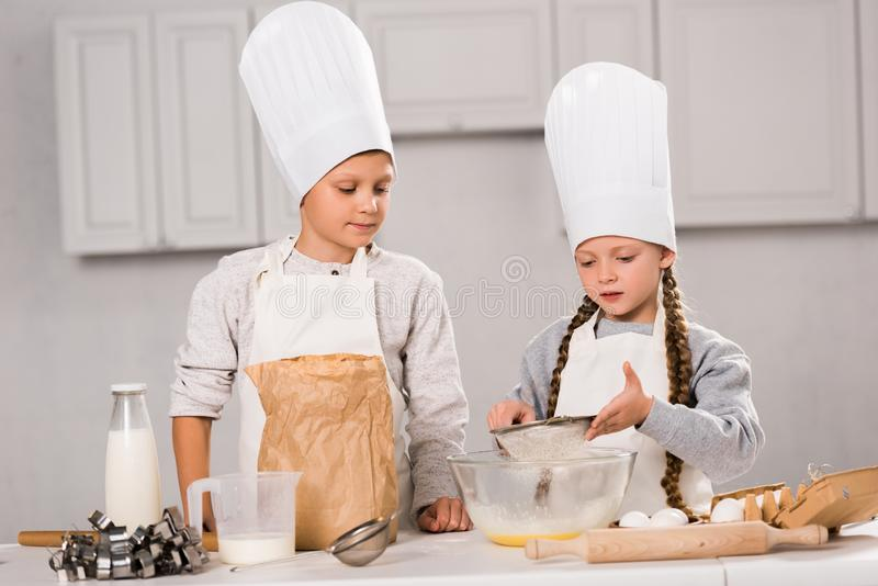 Sister and brother in aprons sifting flour through sieve into bowl at table. In kitchen stock photos