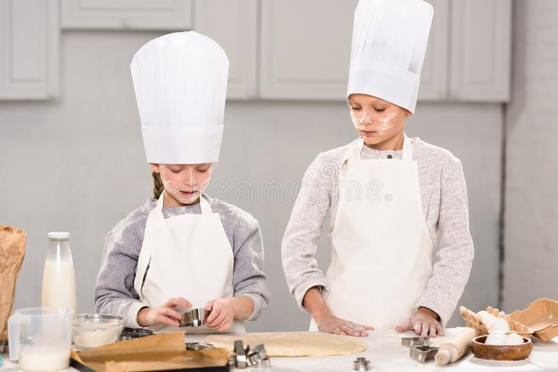 Sister and brother in chef hats and aprons cutting out dough for cookies at table. In kitchen stock image