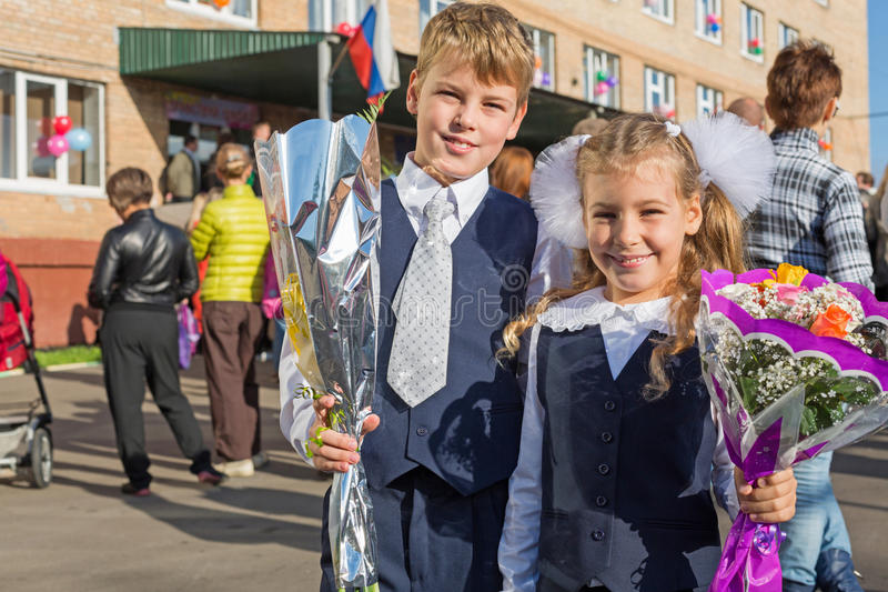 Sister and brother on the first day of school. Sister and brother with the flowers on the first day of school stock images