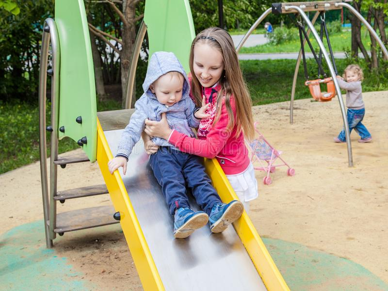 Sister and brother playing on the Playgrou. The girl helps a little boy on a children`s slide. royalty free stock image