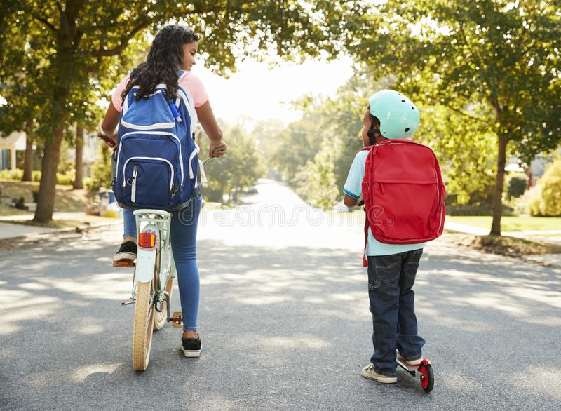 Sister With Brother Riding Scooter And Bike To School royalty free stock photography